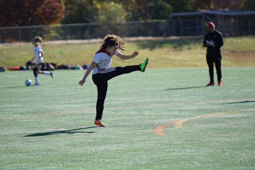 youth athlete practicing her soccer kick
