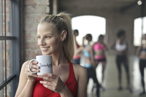 woman smiling and hydrating after a group fitness class